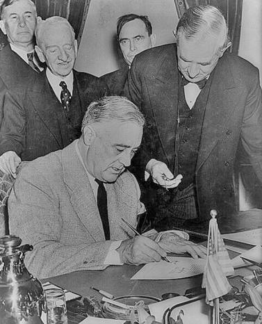 President Roosevelt signs the declaration of war against the Japanese Empire