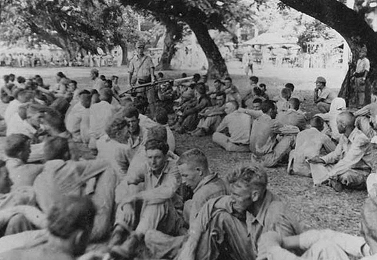 Bataan Death March: Group of American prisoners, note Japanese guard with fixed bayonet. The March of Death was from Bataan to the prison camp march at Cabana Tuan. May 1942.